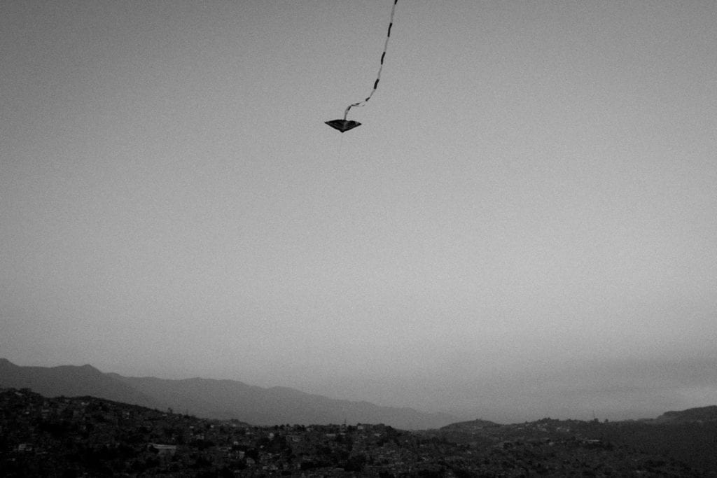 """A kite flies on top of Petare, the biggest """"barrio"""" (slum) in Caracas and second largest in Latin America on March 2016. Kids have the tradition of flying kites inside the barrios of my city. From the series Blurred in Despair."""