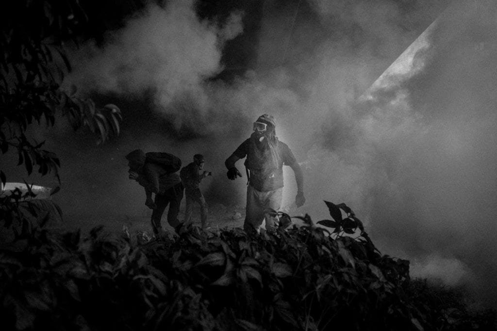 Protesters look for protection from tear gas and rubber under a bridge during a confrontation with the National Guard on April 6, 2017 in Caracas, Venezuela. From the series Blurred in Despair.