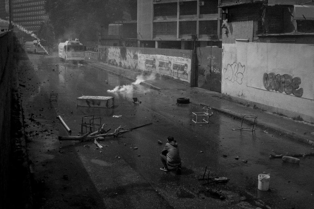A young protester waits for the water canon to come to him during an opposition demonstration that ended up in a 4 hour confrontation with the security forces in Caracas, April 6, 2017.