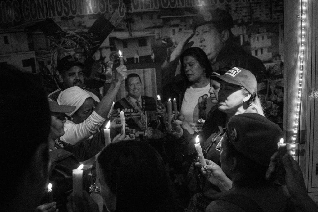 """A group of Venezuela's late president Hugo Chávez's supporters pray to him in the first anniversary of his death. They gathered on a small chapel created in his name (""""Santo Hugo Chávez"""", """"Holly Hugo Chávez"""") after he died from cancer in 2013. Part of the project Blurred in Despair."""