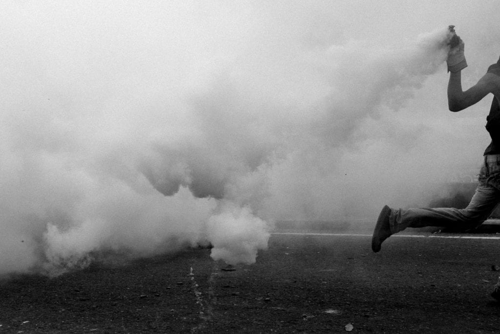 An opposition protester throws back a tear gas bomb during clashes against security forces in Caracas, Venezuela, on April 2017. From the series Blurred in Despair.