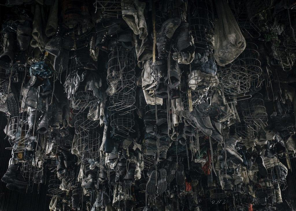 Les vêtements des mineurs sèchent, suspendus à des cages remontées au plafond grâce à des chaînes.