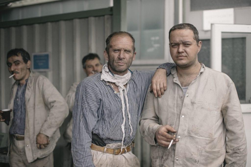 Deux mineurs fument une cigarette après le travail. Des centaines d'entre eux ont quitté cette communauté soudée par des conditions de travail pénible marquées par l'obscurité, la sueur et les obstacles. Les jeunes se reconvertissent et les plus âgés prennent une retraite anticipée, avant l'âge de 49 ans. C'est une cordialité particulière, pas immédiatement perceptible, qui unie les gens.