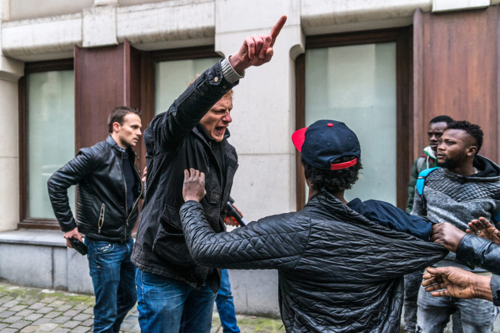 November 2018, Brussels, Belgium. While they try to force the door of an abandoned building they were planing to occupy, a group of undocumented people called VSP, is facing 3 angry unidentified men threatening them with a FN 300 (less lethal weapon) Out what seemed to be a panic reaction, those 3 men who would appear later to be policemen shot 3 times at close range.