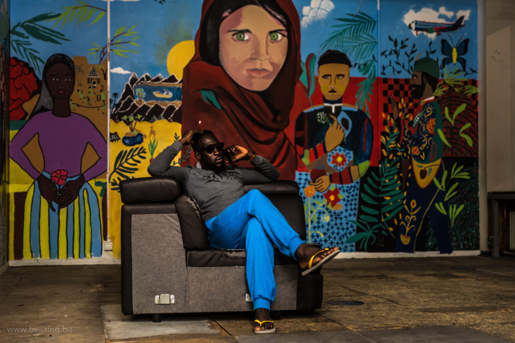 Suleyman (a member of VSP) like a king on his thrown in the main hall of the occupation. This wall painting which includes a reference to the photo of a refugee by Steve Mc Curry was already there before they moved in.