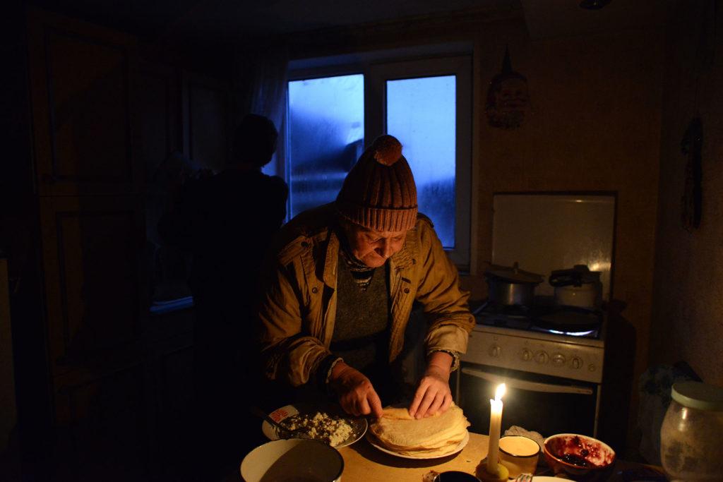 Masha dans sa cuisine, il est16h 30la nuit tombe, sans éléctricité, elle s'éclaire à la bougie pour cuisiner et garde son manteau car la cuisine n'est que faiblement chauffé.Barmoutka, Est de l'Ukraine, Novembre 2016.©Péhée Marion